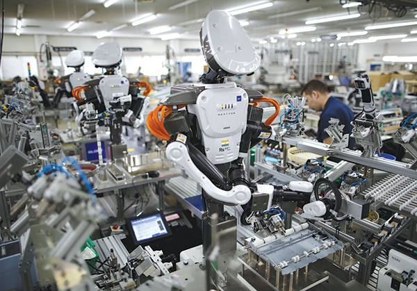 Humanoid robots work side by side with employees in the assembly line at a factory of Glory Ltd., a manufacturer of automatic change dispensers, in Kazo, north of Tokyo