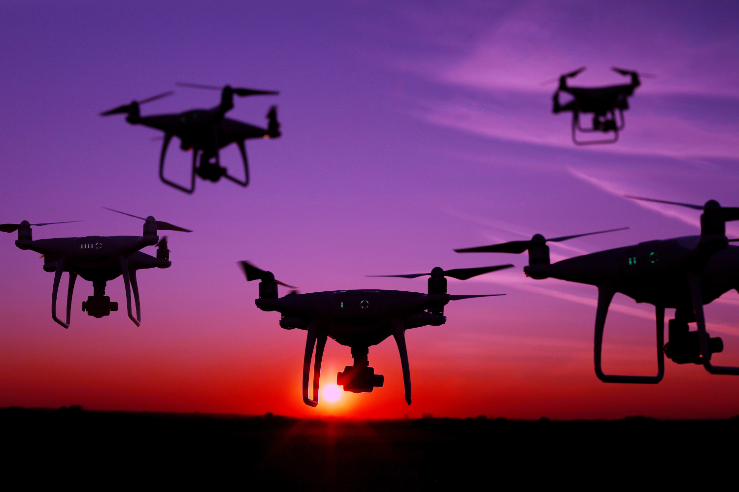 Five drones in the sky at sunset